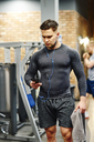 Man using cell phone at the gym - ABIF00251