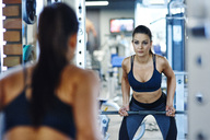 Woman lifting barbell in gym looking in mirror - ABIF00254