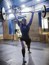 Woman lifting barbell in gym - ZEDF01261