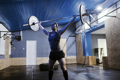 Woman lifting barbell in gym - ZEDF01264
