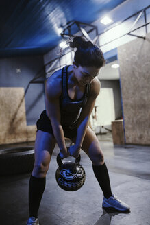 Woman exercising with a kettlebell in gym - ZEDF01267
