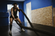 Woman exercising with ropes in gym - ZEDF01270