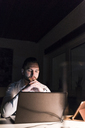 Portrait of businessman sitting at desk  in office at night looking at laptop - UUF13197