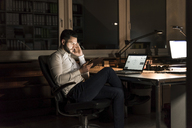 Businessman using tablet in office at night - UUF13200