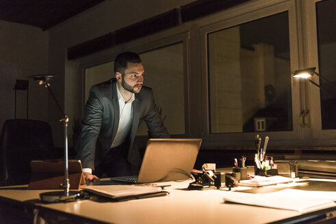 Businessman working in office at night - UUF13203