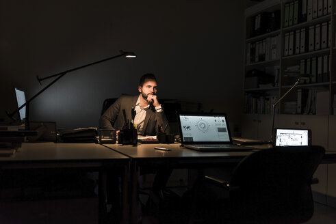 Pensive businessman sitting at desk in office at night - UUF13206