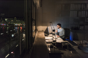 Businessman working on computer in office at night - UUF13212