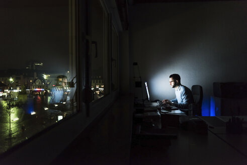 Businessman working on computer in dark office - UUF13215