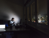 Exhausted businessman sitting at desk in his office by night - UUF13218