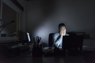 Exhausted businessman sitting at desk in office at night - UUF13221