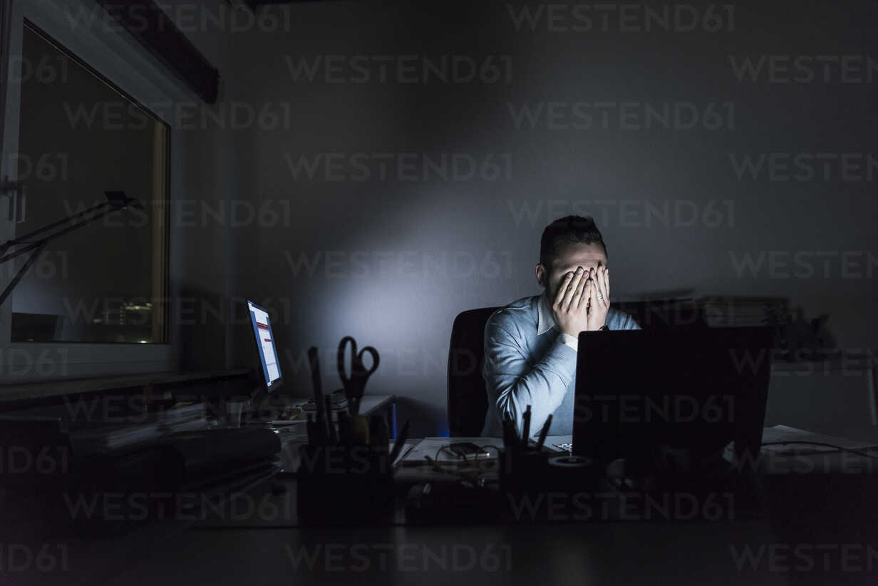 Exhausted businessman sitting at desk in office at night - UUF13221 - Uwe Umstätter/Westend61