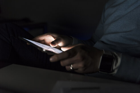 Businessman working on tablet at night, close-up - UUF13227