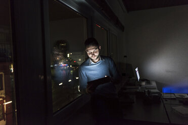 Businessman sitting on window sill in office at night using tablet - UUF13230
