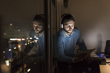 Businessman sitting on window sill in office at night using tablet and headphones - UUF13233