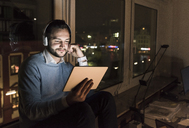 Businessman sitting on window sill in office at night using tablet and headphones - UUF13236