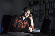 Portrait of freelancer sitting at desk at night using laptop and headphones - UUF13245