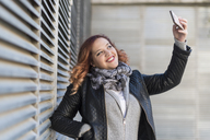 Portrait of happy young woman taking selfie with smartphone - JASF01859