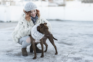 Happy young woman with her dog in winter - JASF01871
