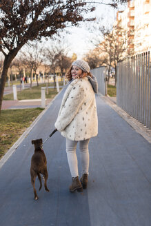 Happy young woman going walkies with her dog - JASF01877