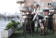 Young woman sitting on on terrace of a pub in winter with her dog using cell phone - JASF01880