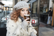 Portrait of young woman drinking beer on terrace of a pub in winter - JASF01883