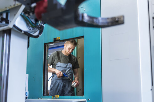 Man working at machine in factory - DIGF03657
