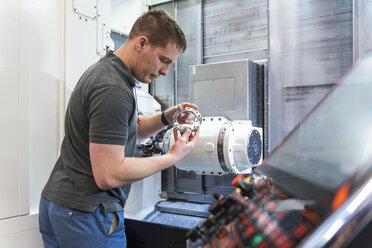 Man examining workpiece at machine in factory - DIGF03666
