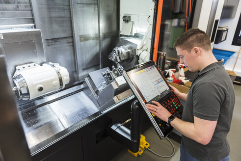 Man operating machine in factory - DIGF03669