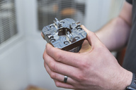 Close-up of man holding workpiece in factory - DIGF03678