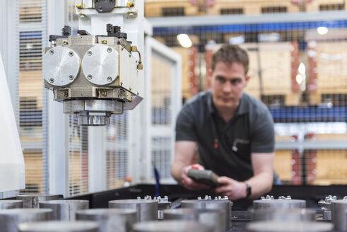 Man operating machine in factory - DIGF03681