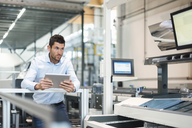 Businessman with tablet looking at machine in modern factory - DIGF03705