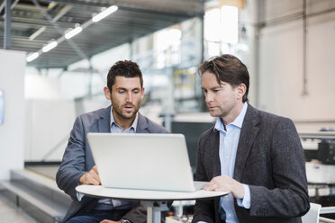 Two businessmen sharing laptop in factory - DIGF03723