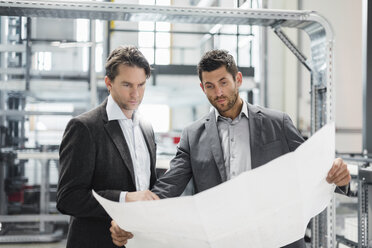 Two businessmen looking at plan in modern factory - DIGF03726