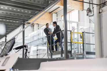Two businessmen talking in modern factory - DIGF03735