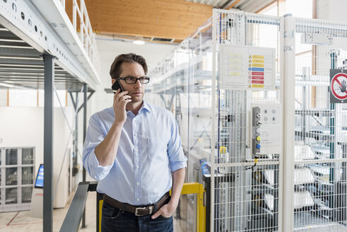 Businessman on cell phone in factory - DIGF03738