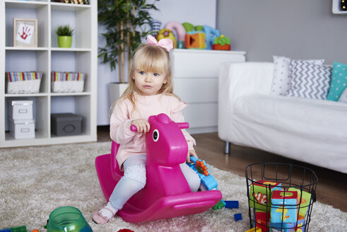 Portrait of little girl sitting on pink rocking horse in the living room - ABIF00257