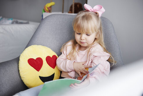 Portrait of blond little girl sitting in arm chair looking at picture book - ABIF00263