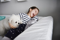 Laughing little girl playing with dog on the couch in the living room - ABIF00269