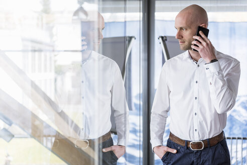 Businessman on cell phone in office - DIGF03760