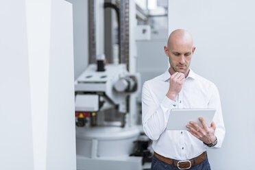 Businessman using tablet in modern factory - DIGF03787