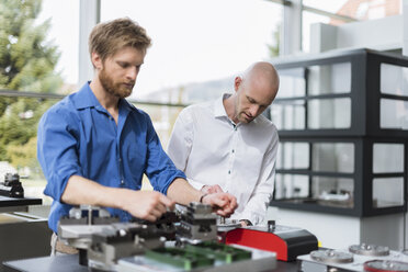 Two men working on product in company - DIGF03796