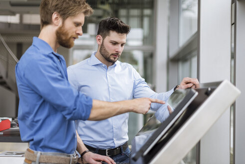 Two businessmen in company using touchscreen - DIGF03799