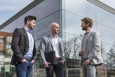 Three businessmen standing outside office building talking - DIGF03811