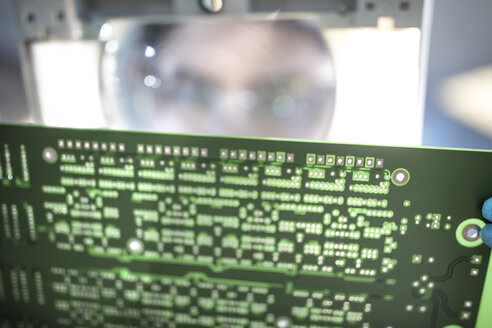 Technician examining motherboard with magnifying glass - ZEF15269