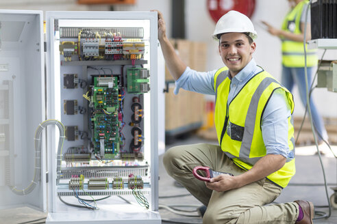 Portrait of smiling technician working on a box with circuit boards - ZEF15299