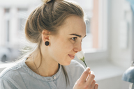 Smiling young woman smelling blossom - GUSF00615