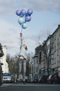 Young woman with blue balloons jumping in the air on the street - GUSF00618