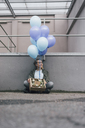 Smiling woman with flowers in cardboard box and bunch of blue balloons sitting on ground - GUSF00621