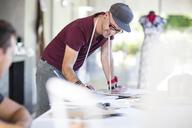 Smiling fashion designer taking notes on table - ZEF15305