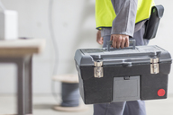 Close-up of construction worker carrying tool box - ZEF15347